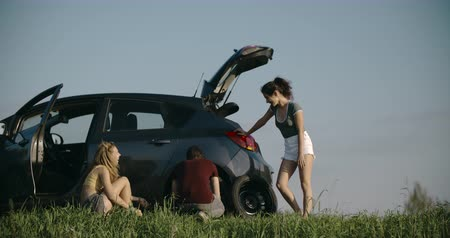 beira da estrada : Cute woman jacking up her car to change flat tire Stock Footage