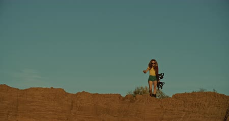 snowbord : woman sandboarder on a cliff, sunset light Wideo