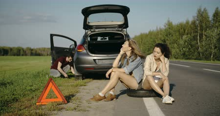 beira da estrada : Broken wheel man changing tire help two female friends looking around