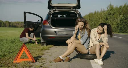 beira da estrada : Broken wheel man changing tire help two sad female friends Stock Footage