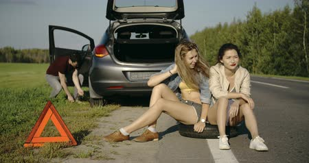 beira da estrada : Broken wheel man changing tire help two female friends wait