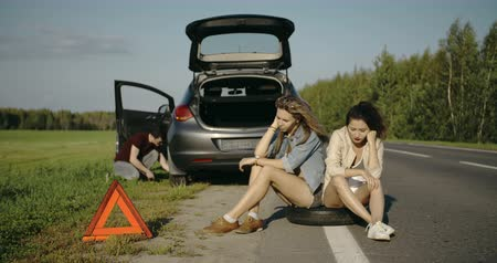 beira da estrada : Broken wheel man changing tire help two female friends waiting
