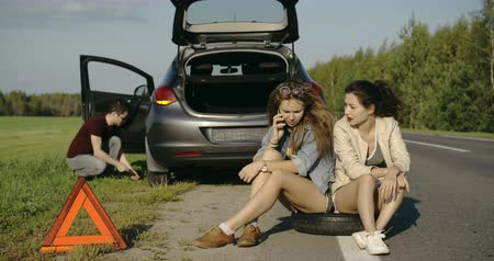 beira da estrada : Broken wheel man changing tire help two female friends looking for help Stock Footage