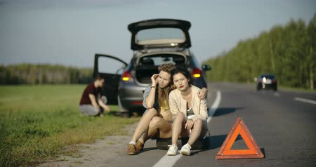 beira da estrada : Broken wheel man changing tire help two female friends boring