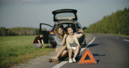 beira da estrada : Puncture wheel man changing tire help two female friends take selfie