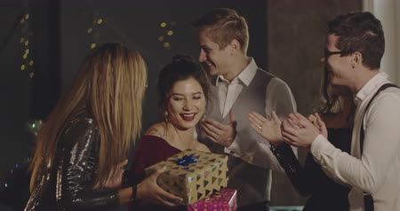 tebrik etmek : Young people presenting gifts to a beautiful birtday girl. Christmas, friendship, birthday, new year, lifestyle, advertising, commercial concept. Medium shot on 4k RED camera with 12 bit color depth. Stok Video