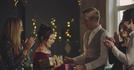 invite : Young people presenting gifts to a woman who has invited them. Christmas, friendship, new year, lifestyle, advertising, commercial concept. Medium shot on 4k RED camera with 12 bit color depth. Stock Footage