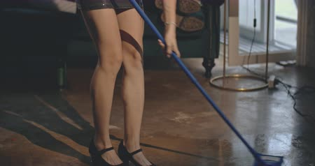bafat : Angry woman cleaning up the house after xmas party, drunk man in background. Christmas, friendship, vacation, advertising, commercial concept. Close shot on 4k RED camera with 12 bit color depth. Dostupné videozáznamy