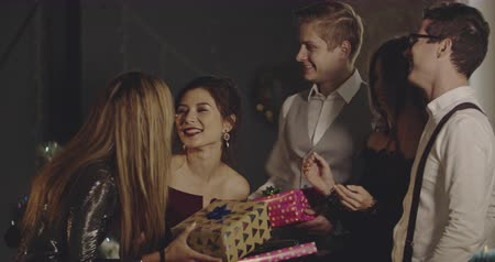 tebrik etmek : Cheerful young people presenting gifts to a birtday girl. Christmas, friendship, birthday, new year, lifestyle, advertising, commercial concept. Medium shot on 4k RED camera with 12 bit color depth. Stok Video