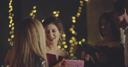 tebrik etmek : Cheerful young friends congratulating and hugging a birtday girl. Xmas, friendship, birthday, ny, lifestyle, ad, commercial concept. Close shot on 4k RED camera with 12 bit color depth. Stok Video