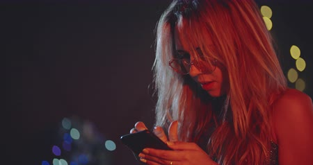чат : Lonely blonde girl tapping messages at xmas eve. Christmas, new year, birthday, party, fashion, lifestyle, advertising, commercial concept. Close shot on 4k RED camera with 12 bit color depth. Стоковые видеозаписи