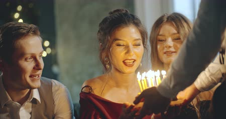 специальный : Man brings cake with candles to a birthday girl, home party. Birthday, party, family, friendship, lifestyle, advertising, commercial concept. Close shot on 4k RED camera with 12 bit color depth.