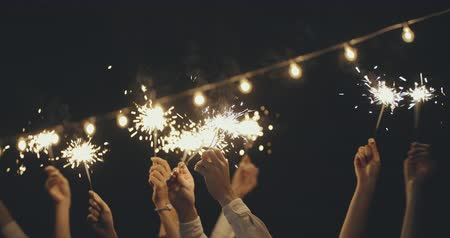 bengália : People waving sparklers celebrating xmas. Christmas, friendship, vacation, lifestyle, advertising, commercial concept. Close shot on 4k RED camera with 12 bit color depth. Stock mozgókép