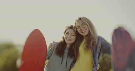 nástup do letadla : Portrait of two girls standing in the desert, hugging each other and holding sandboards. Sport, friendship, lifestyle, commercial, advertisement concept. Shot on 4k RED camera with 12 bit color depth.