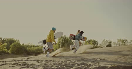 nástup do letadla : Friends running uphill with sandboards in hands in the desert. Sport, tourism, lifestyle, commercial, advertisement concept. Shot on 4k RED camera with 12 bit color depth.