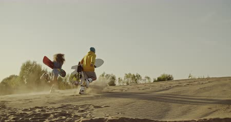 nástup do letadla : Three friends running uphill with sandboards in hands in the desert. Sport, tourism, lifestyle, commercial, advertisement concept. Shot on 4k RED camera with 12 bit color depth.