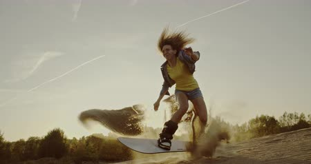 nástup do letadla : Millenial woman jumping on sandboard in the desert. Sport, tourism, lifestyle, commercial, advertisement concept. Shot on 4k RED camera with 12 bit color depth.
