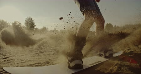 riskantní : Man doing tricks on sandboard in the desert at sunset. Sport, tourism, lifestyle, commercial, advertisement concept. Shot on 4k RED camera with 12 bit color depth.