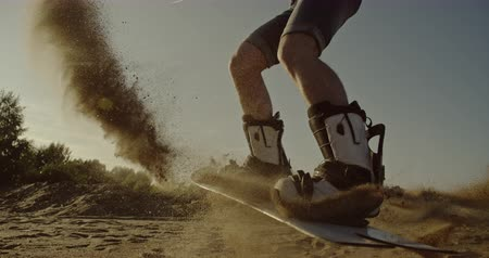 riskli : Young man jumping on sandboard in the desert at sunset. Sport, tourism, lifestyle, commercial, advertisement concept. Shot on 4k RED camera with 12 bit color depth. Stok Video