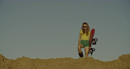 nástup do letadla : Hot fashion girl with sandboard in desert. Sport, tourism, lifestyle, commercial, advertisement concept. Shot on 4k RED camera with 12 bit color depth.