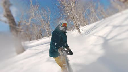 sırıtma : snowboarder making ttrick on snowboard in powder day frame shot on a freeride tour in Kamchatka volcanoes Stok Video