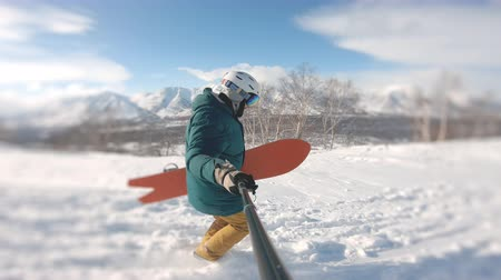 narciarz : snowboarders going uphill in powder day, holding boards, filmed on the action camera, frame shot on a freeride tour in Kamchatka volcanoes, filmed on the action camera Wideo