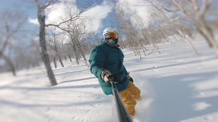 sırıtma : Proffesional sportsman riding in powder day, frame shot on a freeride tour in Kamchatka volcanoes, filmed on action camera