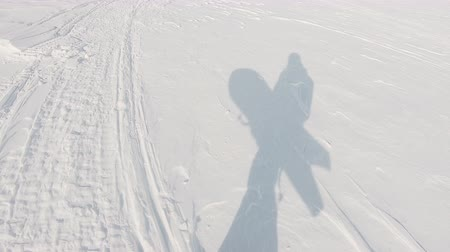 ライダー : snowboarder shadow on snow, frame shot on a freeride tour in Kamchatka volcanoes, filmed on the action camera 動画素材