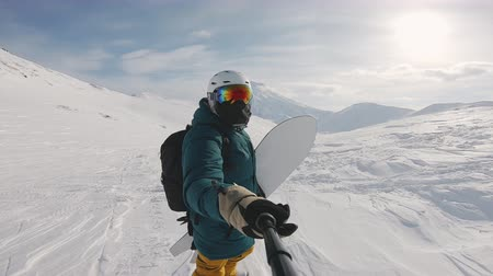 narciarz : snowboarder selfie in powder day, holding boards, filmed on the action camera, frame shot on a freeride tour in Kamchatka volcanoes, filmed on the action camera