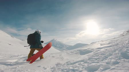 ski freestyle : snowboarder walks uphill, holding boards, filmed on the action camera, frame shot on a freeride tour in Kamchatka volcanoes, filmed on the action camera in protune mode