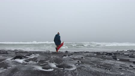 freeride : snowboarder walking along the black sand beach, backcountry, filmed on the action camera, frame shot on a freeride tour in Kamchatka volcanoes, filmed on the action camera in protune mode Stock Footage