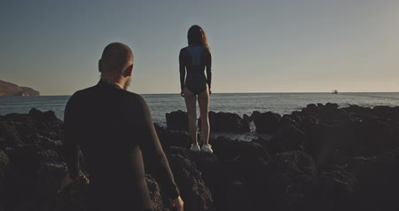 meghittség : Weird freediver couple in wetsuites standing on rocks at sunset, filmed on cinematic camera, 12 bit color