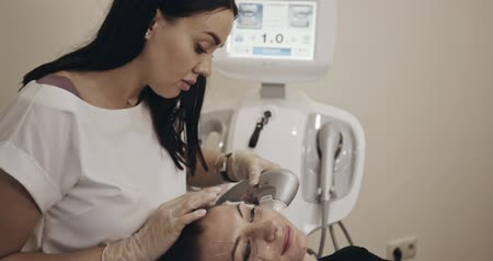 stárnutí : Non-surgical face lifting. Beautician using device. Filmed on cinema camera, 12 bit color