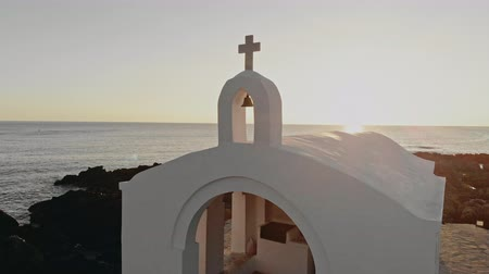 biblia : White Greek church at sunset, seaside, filmed on drone