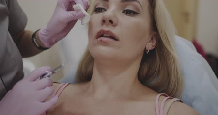 lekke band : Beautician doing lip injection for a lady in her clinic, Shot on cinema canera, 12 bit color depth