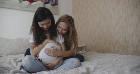 lesbijki : Happy lgbt family waiting a baby and looking at ultrasound picture. Lgbt, homosexual, pride, bisexual, gay lovewins equality, loveislove friendship, concept. Filmed on RED, 12 bit color, 4k