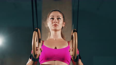 broca : Athletic Beautiful female Exercises with rings in a Gym. Sport, fitness, lifestyle, beauty concept. Filmed on cinemacamera.