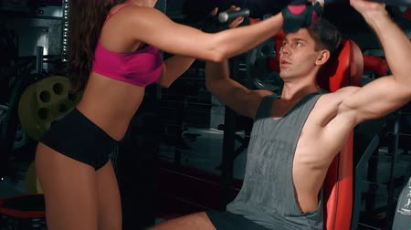 broca : Female trainer helps to a man in a gym. Sport, fitness, lifestyle, beauty concept. Filmed on cinemacamera. Stock Footage
