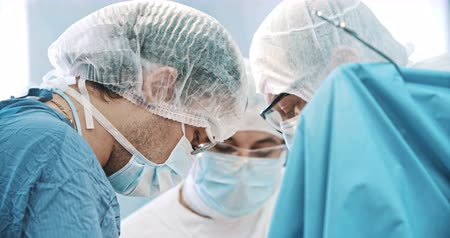 liposukcja : Surgeons bowing heads above a patient in operating room. Medicine, surgery, health care concept. Filmed on RED 4k, 10 bit color space Wideo