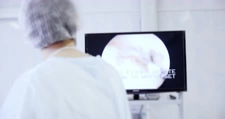 utero : Back view of surgeon looks at monitors while preforming operation using surgical laparoscopy instruments. Medicine, surgery, health care concept. Filmed on RED 4k, 10 bit color space Filmati Stock
