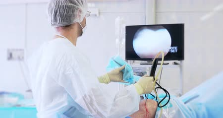 utero : Back view of surgeon looking at monitors while preforming operation using surgical laparoscopy instruments. Medicine, surgery, health care concept. Filmed on RED 4k, 10 bit color space