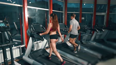 broca : Couple of friends running in gym together. Sport, fitness, lifestyle, beauty concept. Filmed on cinemacamera. Stock Footage