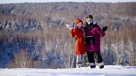 cavalcare : Happy coulple waving hands to camera in mountain ski resort at sunny day. Winter, sport, holidays, relationship, love, xmas, lifestyle concept. Filmed on cinema camera, 10 bit color space.