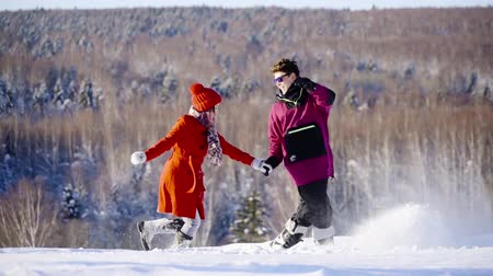 girfriend : Happy coulple running inslow motion in mountain ski resort at sunny day. Winter, sport, holidays, relationship, love, xmas, lifestyle concept. Filmed on cinema camera, 10 bit color space.