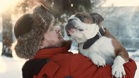 tlapky : Bearded man hugging his bulldog at winter sunny day. Friendship, xmas, winter, pet concept.