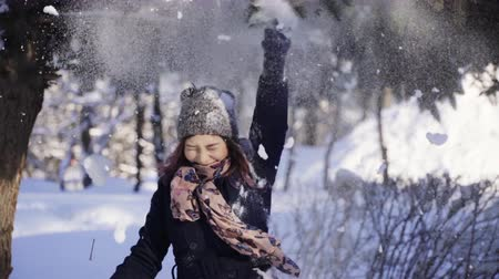 hófúvás : Happy young woman pulling the snowy branch of tree over her head. Winter, sport, holidays, relationship, love, xmas, lifestyle concept. Filmed on cinema camera, 10 bit color space.