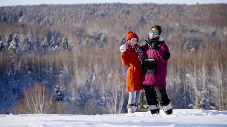 girfriend : Happy young coulple waving hands to camera in mountain ski resort at sunny day. Winter, sport, holidays, relationship, love, xmas, lifestyle concept. Filmed on cinema camera, 10 bit color space. Stock Footage