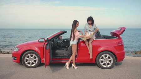 kabriolet : Two glamorous girls on cabriolet exploring the map. Travel, lifestyle. luxury, freedom, blogging concept.