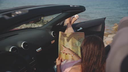 decapotable : Woman studying the map in cabriolet. Travel, lifestyle. luxury, freedom, blogging concept. Vidéos Libres De Droits