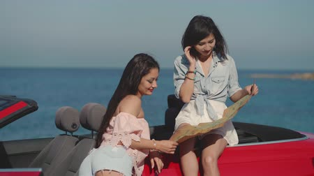 kabriolet : Two luxury looking girls on cabriolet exploring the map. Travel, lifestyle. luxury, freedom, blogging concept.